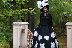 Flicka i gammal retro klänning på utomhus- trappa Royaltyfria Bilder