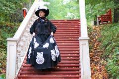 Flicka i gammal retro klänning på utomhus- trappa Fotografering för Bildbyråer