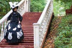 Flicka i gammal retro klänning på utomhus- trappa Royaltyfria Foton