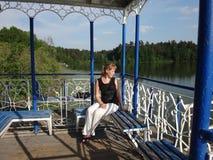 Flicka i gazeboen på sjön Arkivbild