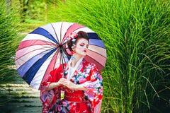 Flicka i geishadräkt med ett paraply Arkivfoto