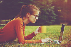 Flicka i gräs genom att använda bärbar datormaskinskrivning Royaltyfri Foto