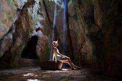 Flicka i grottan under solstrålar Fotografering för Bildbyråer