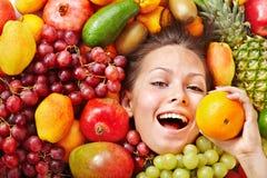 Flicka i grupp av frukt. Arkivbilder