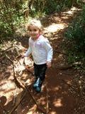 Flicka i gummistöveler som går för en gå i en solig skog arkivbilder