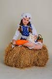 Flicka i höet som matar morötterna för påskkanin Arkivfoto