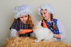 Flicka i höet som matar morötterna för påskkanin Fotografering för Bildbyråer