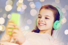 Flicka i hörlurar med smartphonen över ljus Arkivbilder