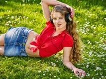 Flicka i hörlurar och musik för rytm för grov bomullstvillkjollås royaltyfria bilder
