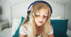 Flicka i hörlurar i sängcloseup arkivfilmer