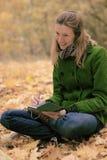 Flicka i höstsidor med en anteckningsbok Arkivfoto