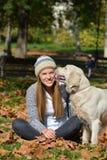 Flicka i höstsidor och hund Royaltyfri Foto