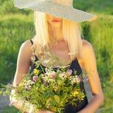 Flicka i hatt med blommor Arkivbilder
