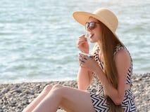 Flicka i hatt som äter glass på stranden solig dag royaltyfri fotografi