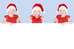 Flicka i hatten av Santa Claus som pekar fingret på annonsstället Royaltyfri Foto
