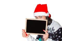 Flicka i hatten av Santa Claus som rymmer ett tecken Fotografering för Bildbyråer