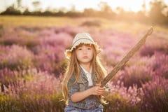Flicka i hatten som spelar med den utomhus- pinnen Royaltyfri Foto