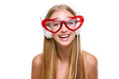 Flicka i hörlurar och hjärta formade exponeringsglas Arkivbilder