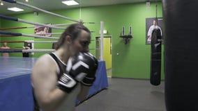 Flicka i idrottshallboxningen med en boxas påse arkivfilmer