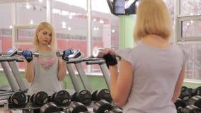 Flicka i idrottshallen lager videofilmer