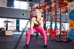 Flicka i idrottshallen som gör övning med rep royaltyfria bilder