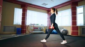 Flicka i idrottshallen som gör utfall med hantlar Övning på musklerna av låret och bakdelarna lager videofilmer