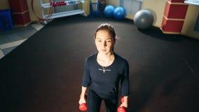 Flicka i idrottshallen som gör utfall med hantlar Övning på musklerna av låret och bakdelarna stock video