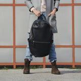Flicka i jeans, bruna kängor och grå en blazer som framme rymmer en stor svart läderryggsäck, ryggsäck av henne royaltyfria bilder