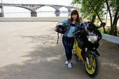 Flicka i jeans med en motorcykel arkivbilder