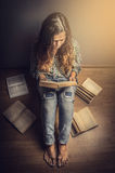 Flicka i jeans och en plädskjorta med det långa sammanträdegolvet för krabbt hår som läser en retro toning för bok fotografering för bildbyråer