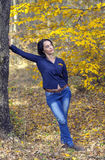 Flicka i jeans som lutar i höstskog Arkivfoto