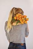 Flicka i jeans som rymmer orange tulpan Royaltyfri Fotografi