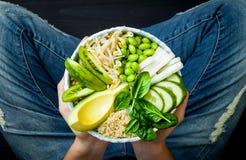 Flicka i jeans som rymmer strikt vegetarian, grön Buddhabunke för detox med quinoaen, avokado, gurka, spenat, tomater, mung böngr arkivbilder