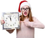 Flicka i julhatt med klockan Fotografering för Bildbyråer