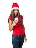 Flicka i jultomten en hjälpredahatt med telefonen Fotografering för Bildbyråer