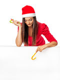 Flicka i jultomten ett anseende för hjälpredahatt nära ett stort vitt bräde och Royaltyfri Bild