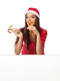 Flicka i jultomten ett anseende för hjälpredahatt nära ett stort vitt bräde och Arkivfoton