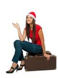 Flicka i jultomten ett sammanträde för hjälpredahatt på en resväska Arkivbild