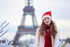 Flicka i jultomtenhatt nära Eiffeltorn royaltyfri fotografi