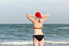 Flicka i jultomtenhattar med det nya året för inskrift på baksidan Händer bak huvudet ovanför havskustsikt tillbaka sikt Arkivbilder