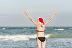Flicka i jultomtenhattar med det nya året för inskrift på baksidan ovanför havskustsikt Händer som lyfts upp tillbaka sikt Arkivfoto