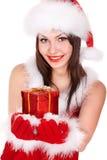 Flicka i jultomtenhatten som ger julasken. Fotografering för Bildbyråer