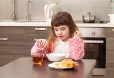 Flicka i köket på tabellen Barndom Royaltyfri Fotografi