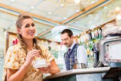 Flicka i kafé eller stång som rör i kaffekoppen, barista i baksida Royaltyfri Fotografi