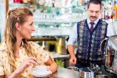 Flicka i kafé eller stång som rör i kaffekoppen, barista i baksida Fotografering för Bildbyråer