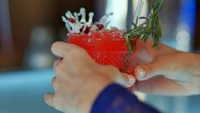 Flicka i kafé med ett exponeringsglas av den röda coctailen som väntar hennes pojkvän Royaltyfri Bild