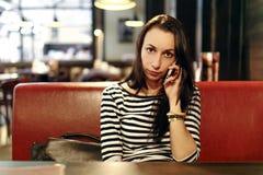 Flicka i kafé med telefonen Royaltyfri Bild