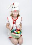 Flicka i kanindräkt med en korg av påskägg Arkivbild