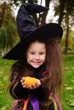 Flicka i karnevaldräkt och i hatt av häxan med liten pumpa i händer på halloween som ler på kameran royaltyfri fotografi