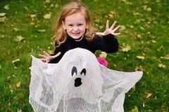 Flicka i karnevaldräkt på halloween med leksakspöken arkivbild